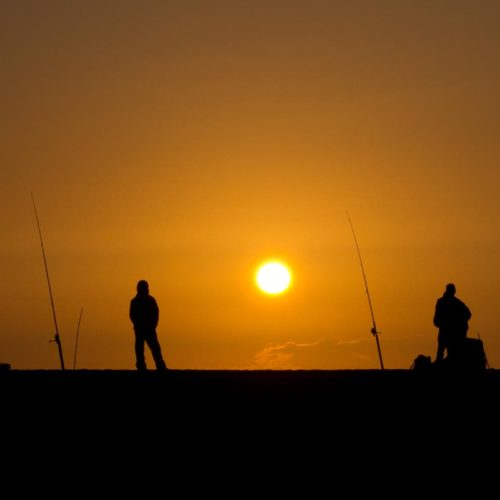 Fisherman silhouettes during sunset