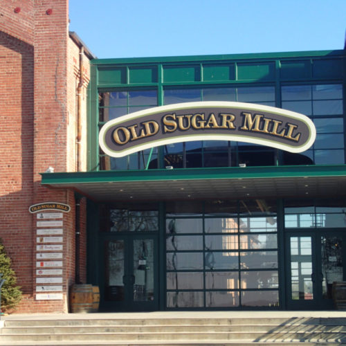 Storefront view of the Old Sugar Mill with sign