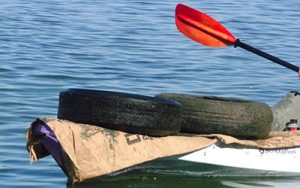 Person on Kayak cleaning up tires in the California Delta